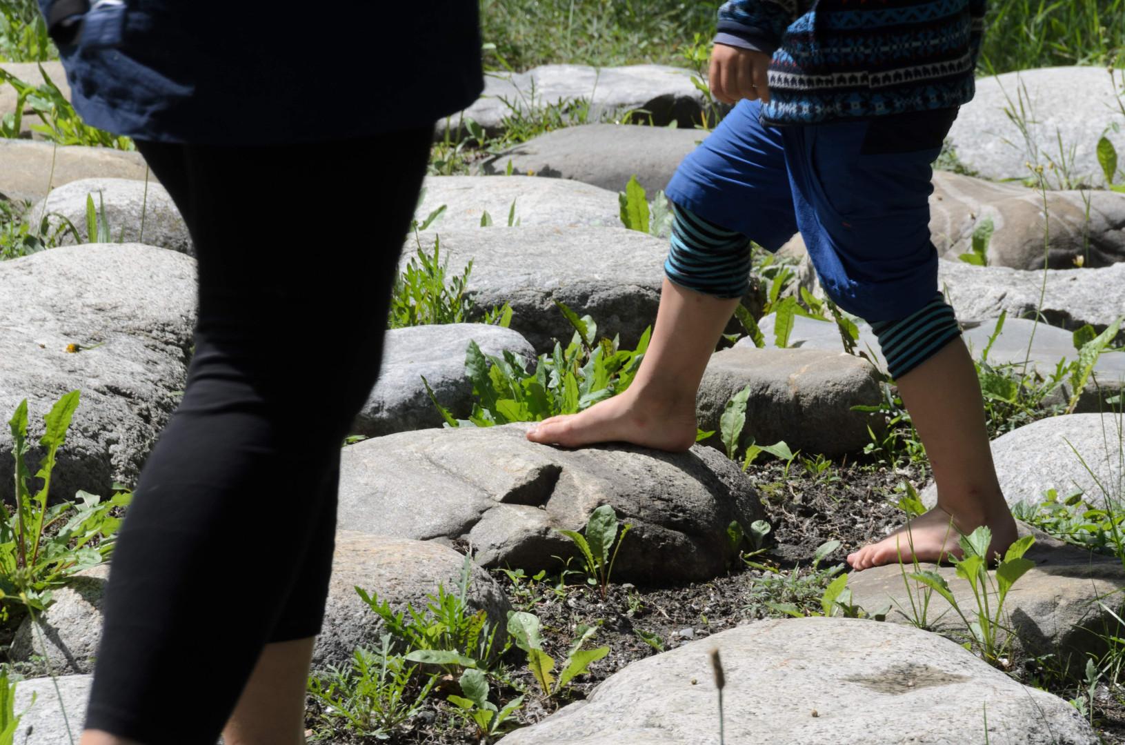 Dieťa a dospelý naboso na veľkých kameňoch v prírode