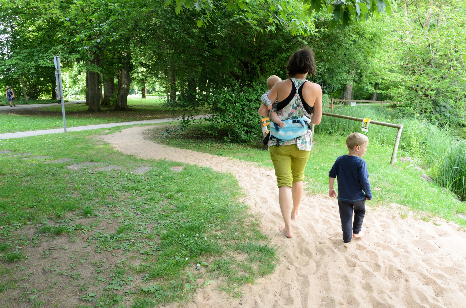 Matka s dvomi deťmi na barefoot chodníku kráča naboso po piesku